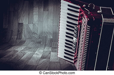 Part pink accordion on wooden grey background Write text