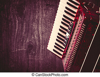 Part red accordion on wooden grey background Write text...