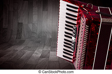 Part red accordion on wooden grey background Write text
