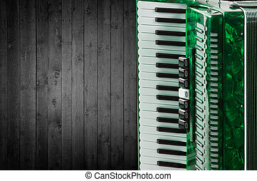 Part green accordion on wooden grey background Write text