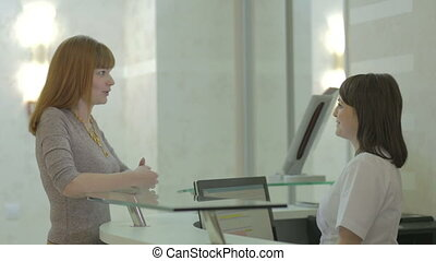 Patient and nurse conversing at hospital reception desk HD