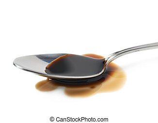 Steel spoon in a puddle of soy sauce isolated over the white...