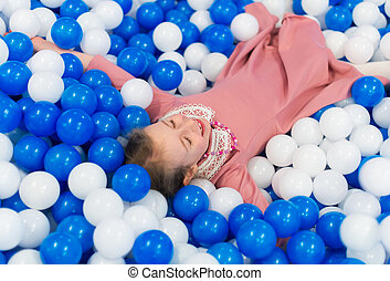 Happy little girl having fun in playroom. Place for text.