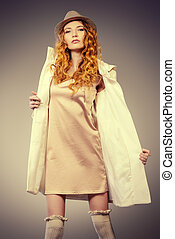 white coat - Sexual female model with curly foxy hair posing...
