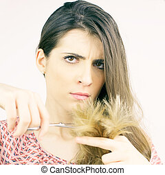Beautiful woman deciding to cut split ends hair looking camera isolated