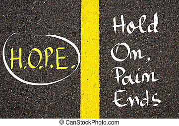 Acronym HOPE as Hold On, Pain Ends written over tarmac, road...
