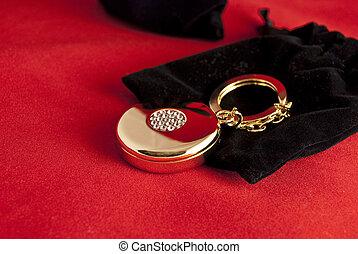 Elegant gold trinket and black velvet bag