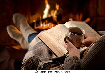 Woman reads book near fireplace - Woman resting with cup of...