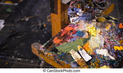 Artist mixes oil paints on pallet with various colors....
