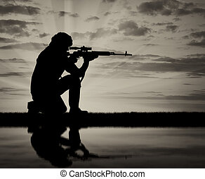 Silhouette of a terrorist with a weapon against a background...