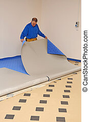laying the carpet - A floorlayer carefully pulls back the...