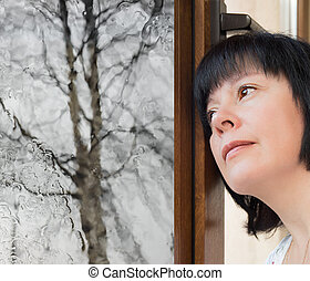 brunette woman looking out the window - Brunette middle-aged...