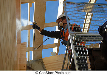 spraying the preservative - Tradesman spray painting the...