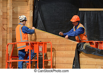 builders measure up - builders measure the wall of a...
