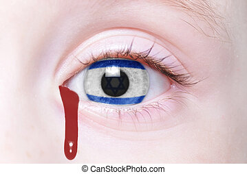 human's eye with national flag of israel with bloody...