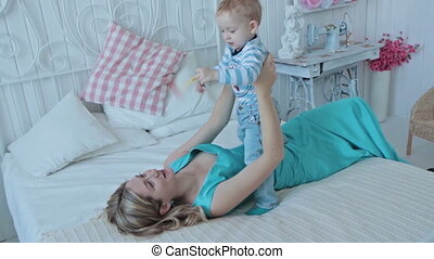 Mother playing with her son at the bedroom
