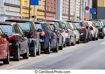 cars parked on the roadside, symbol of parking space,...