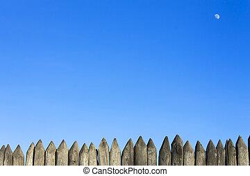 Palisade stockade palings logs and blue sky. Abstract...