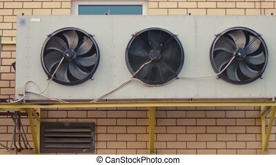 Industrial air conditioning sustem on the wall outdoors. Rotating fans conditioner of an industrial building