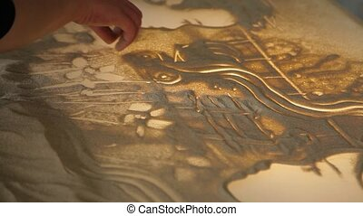 Girl draws painting with sand on the glass