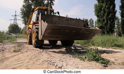 Yellow bulldozer with bucket on the move