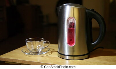 kettle boils - metal electric boiling kettle and a glass cup...