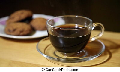 glass cup with coffee and biscuits on a plate closeup