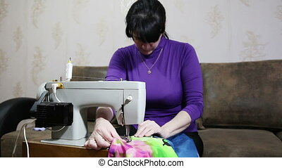 woman sews on the sewing machine - young woman in blue...