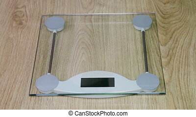 womans legs standing on the scales - womans legs standing on...