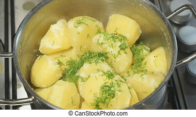 Cooking boiled potatoes with dill in a saucepan