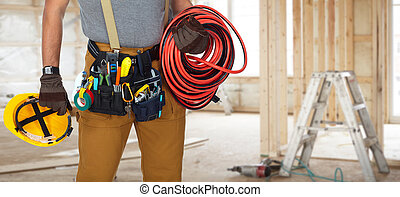 Electrician with construction tools and cable. - Builder...