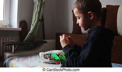 Child Boy Playing with Toys - Child boy sitting on the coach...