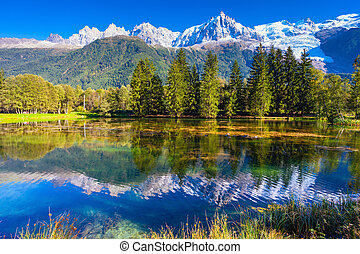 The lake reflected the snow-capped Alps and evergreen spruce...