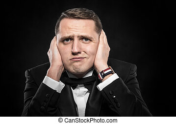 Man covering his ears. - Man in suit covering his ears over...