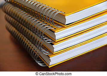 Yellow notebooks stack - four yellow notebooks with ring...