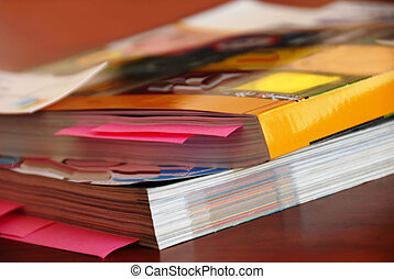 Catalogs - two dense catalogs with bookmarks closeup on desk
