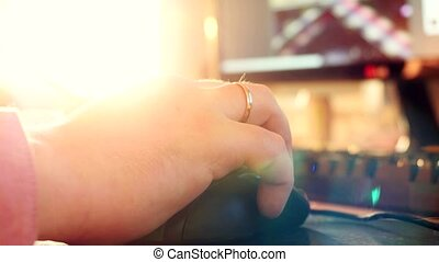 Close up of men hands typing on computer keyboard and mouse with changing focus and lens flare with sunshine. 4k