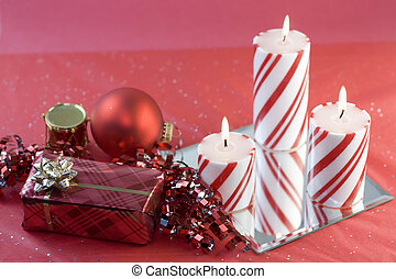 three christmas candles with red decorations
