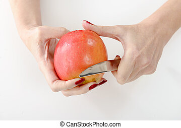 Hands of young woman peeling an apple, isolated on white