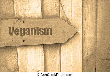veganism sign on wood - arrow sign with the word veganism on...