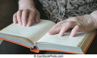Old hands of the old woman holding a book. Closeup