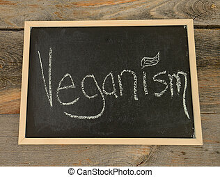 veganism or vegan concept - veganism written in chalk on a...