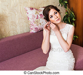 Beautiful bride in white wedding dress puts on earring....