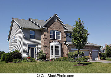 Home with brown brick and gray siding - Suburban home with...