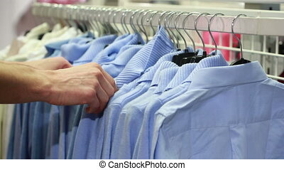 hand clothes shop. blue sweaters and shirts. - male hand...