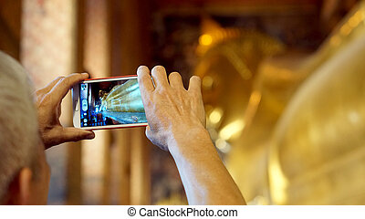 Tourist taking photo with smartphone in temple of sleeping...