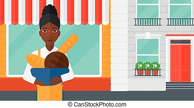 Bakery owner with bread. - An african-american woman holding...