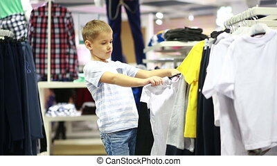 Cute smiling boy stands near clothes and choosing children...