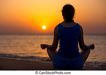 Sukhasana yoga posture - Serene young woman doing yoga...