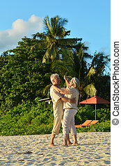 elderly couple dancing at tropical beach - Happy elderly...
